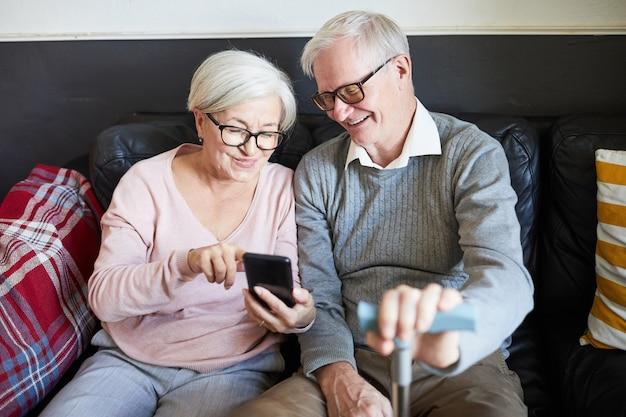 Hoge hoek portret van lachend senior paar met behulp van smartphone in verpleeghuis kopieerruimte