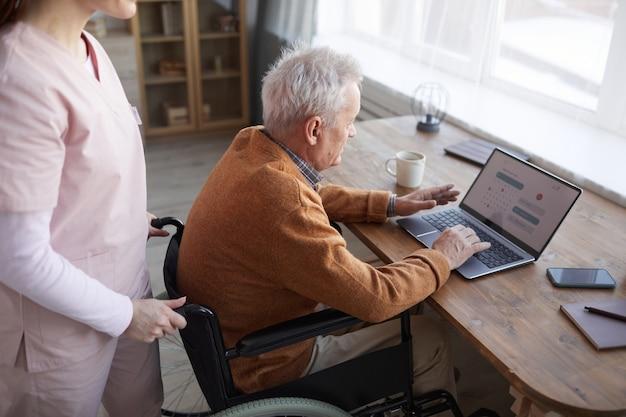 Hoge hoek portret van senior man in rolstoel met behulp van laptop in bejaardentehuis met verpleegster hem bijstaan, kopieer ruimte
