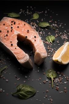 Hoge hoek rauwe zalm steak met peper en citroen