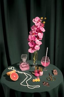 Hoge hoek roze orchidee naast modeartikelen