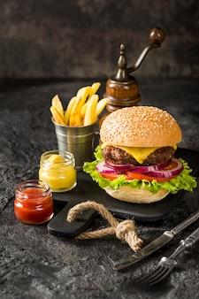 Hoge hoek rundvleesburger op snijplank met friet en saus