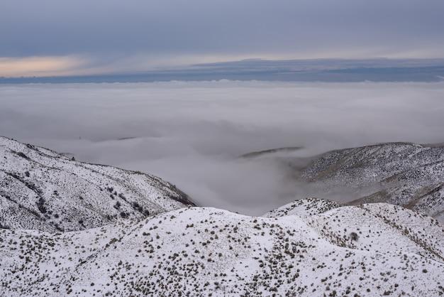 Hoge hoek schot van besneeuwde bergen bedekt met bomen boven de wolken onder een blauwe hemel