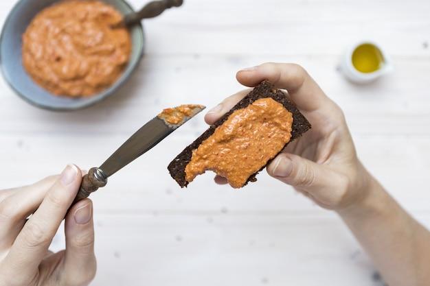 Hoge hoek schot van een persoon die een heerlijke topping op toast met een mes