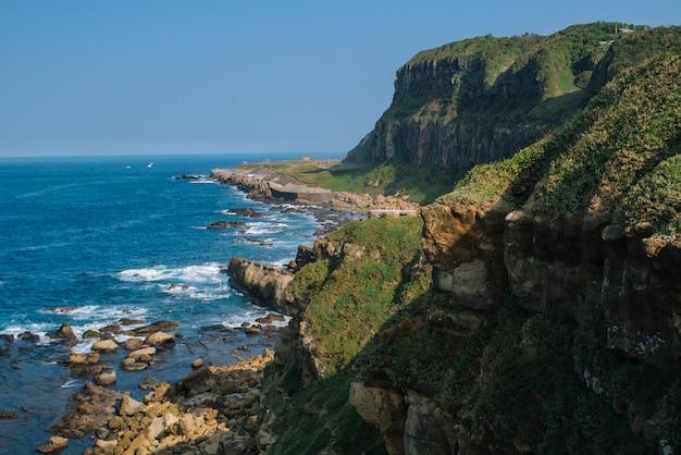 Hoge hoek schot van een prachtige klif bedekt met mos in de buurt van de zee
