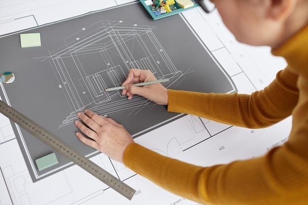 Hoge hoek schot van onherkenbare vrouwelijke architect blauwdrukken en plannen tekenen tijdens het werken aan balie op kantoor,