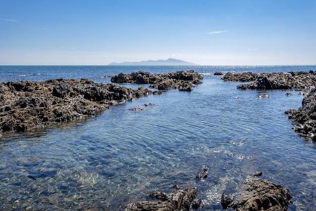 Hoge hoek schot van rotsformaties in het water van pukerua bay in nieuw-zeeland