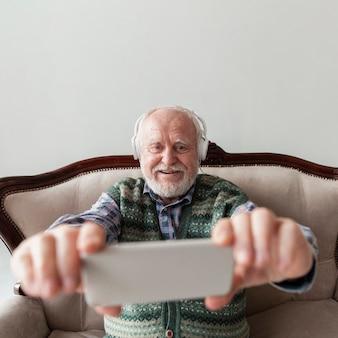 Hoge hoek senior kijken naar videomuziek