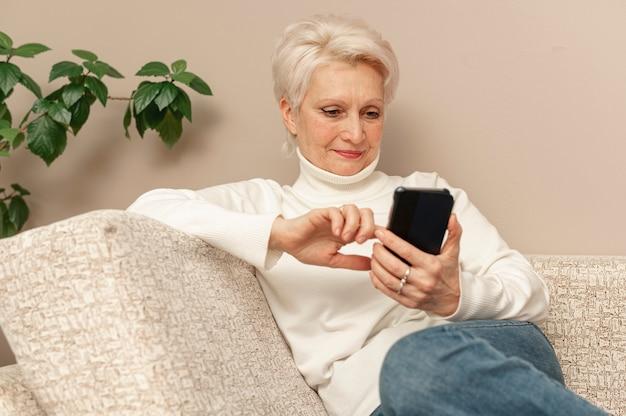 Hoge hoek senior vrouw op bank met behulp van telefoon