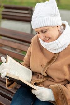 Hoge hoek senior vrouwelijke lezing buiten