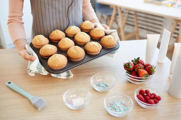 Hoge hoek shot van de onherkenbare vorm van de vrouwenholding met warme cupcakes uit bakoven