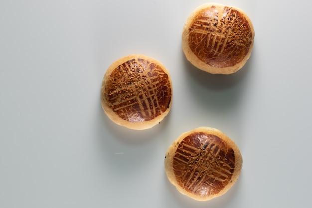 Hoge hoek shot van drie vers gebakken zoete broodjes op een witte ondergrond