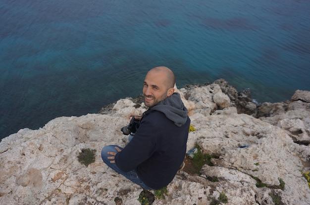 Hoge hoek shot van een glimlachende man zittend op een klif in de buurt van een zee met een camera in zijn hand