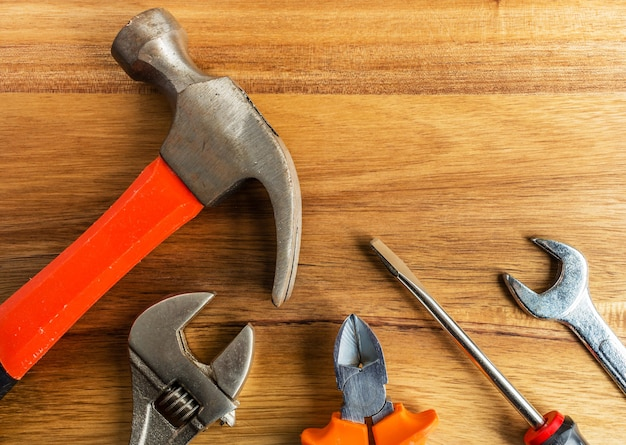 Hoge hoek shot van een hamer, een schroevendraaier en ander gereedschap op een houten oppervlak