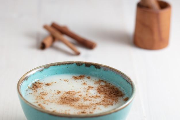 Hoge hoek shot van een kopje melk met kaneel en wat kaneelstokjes op een wit oppervlak
