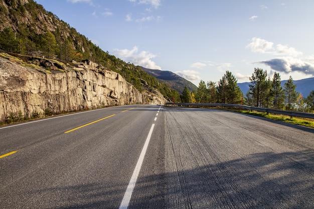 Hoge hoek shot van een lege weg in noorwegen, omringd door bomen en heuvels