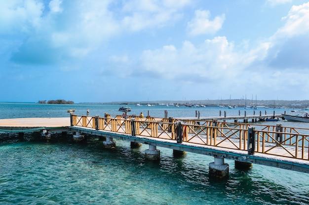 Hoge hoek shot van een pier aan de kust met een bewolkte blauwe hemel