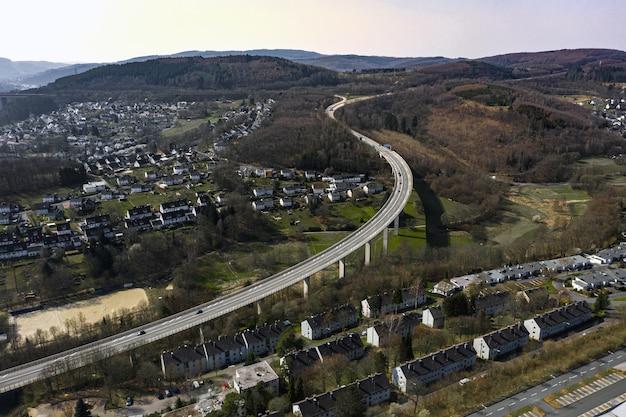 Hoge hoek shot van een prachtige stad, omringd door heuvels onder de blauwe lucht