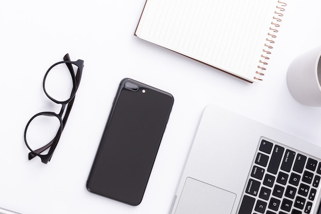 Hoge hoek shot van een smartphone, laptop, bril en een notebook op een witte ondergrond