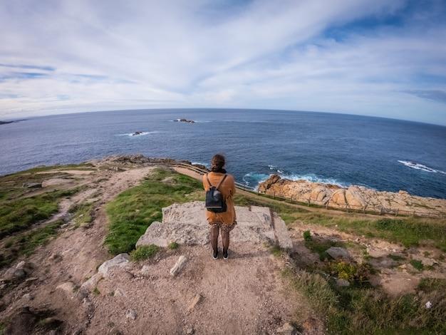 Hoge hoek shot van een stijlvolle vrouw staan en kijken naar de kalme zee in de buurt van coruna, spanje