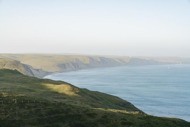 Hoge hoek shot van heuvels bedekt met het groen rondom de oceaan
