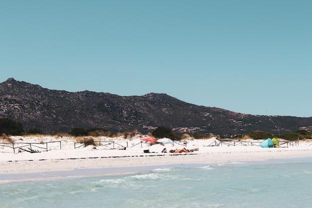 Hoge hoek shot van mensen ontspannen op het strand van san teodoro, sardinië