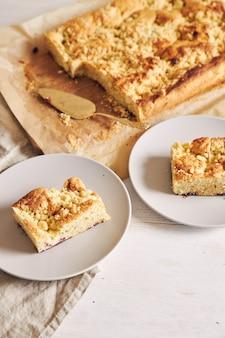 Hoge hoek shot van stukjes heerlijke jerry crumble sheet-cake op een witte houten tafel