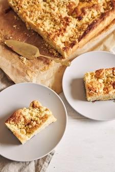 Hoge hoek shot van stukjes heerlijke jerry crumble sheet-cake op witte houten tafel