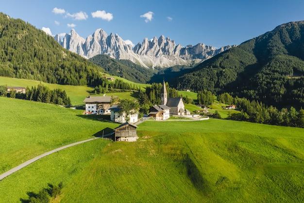 Hoge hoek shot van veel gebouwen omgeven door hoge rotsachtige bergen in funes valley