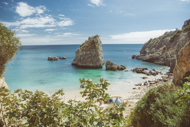 Hoge hoek shot van veel rotsformaties in de buurt van de zee op het strand overdag