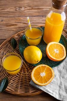 Hoge hoek sinaasappelsap in fles en glas