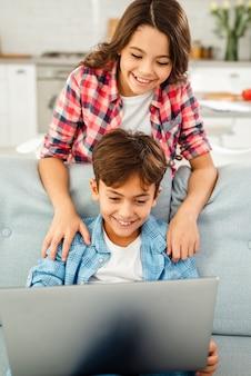 Hoge hoek smiley broers en zussen met laptop