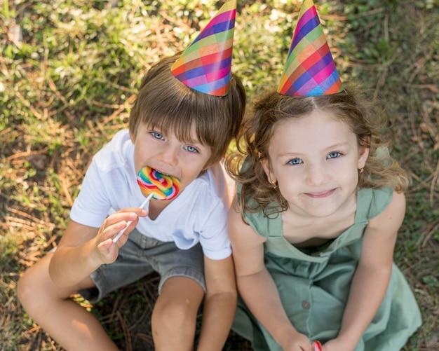 Hoge hoek smiley kinderen met feestmutsen