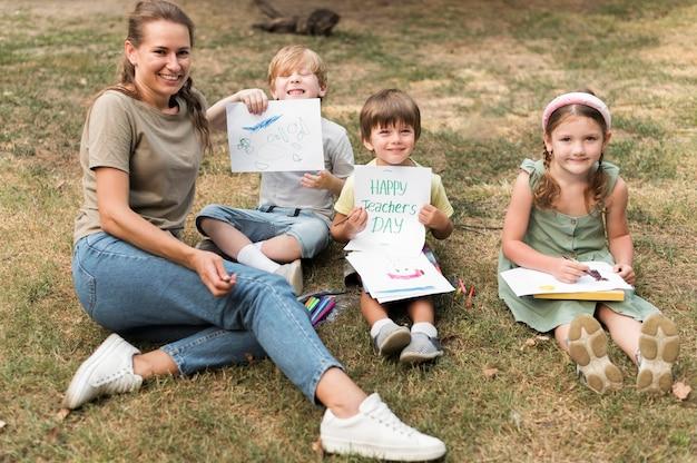 Hoge hoek smiley leraar en kinderen buitenshuis