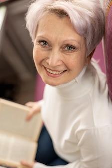 Hoge hoek smiley senior vrouwelijke lezing