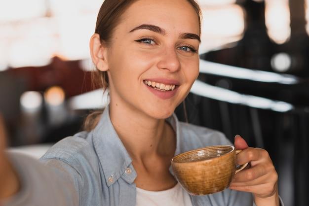 Hoge hoek smiley vrouw koffie drinken
