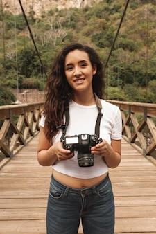 Hoge hoek smiley vrouw met camera op brug