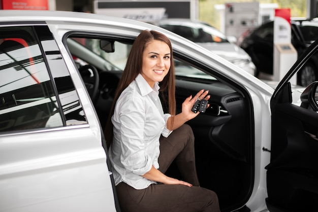 Hoge hoek smiley vrouw zitten in auto