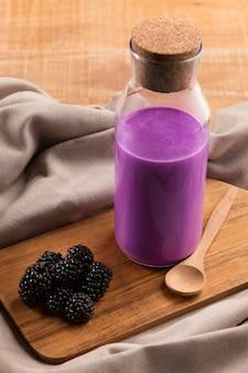 Hoge hoek smoothie in fles met bramen