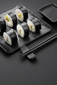 Hoge hoek sushi rollen met stokjes en saus