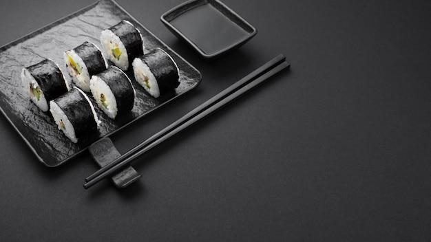 Hoge hoek sushi rollen op leisteen met kopie ruimte