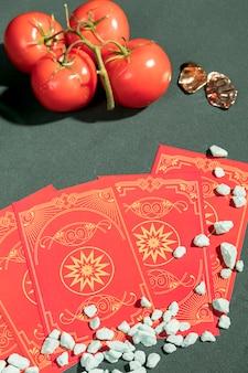 Hoge hoek tarotkaarten naast tomaten