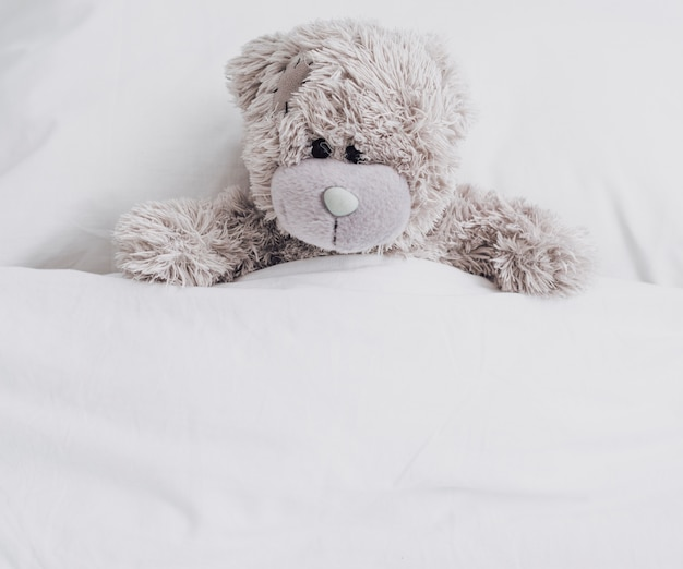 Hoge hoek teddybeer in bed