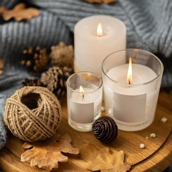 Hoge hoek van aangestoken kaarsen met koord en dennenappels