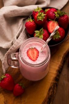 Hoge hoek van aardbeienmilkshake met stro en doek