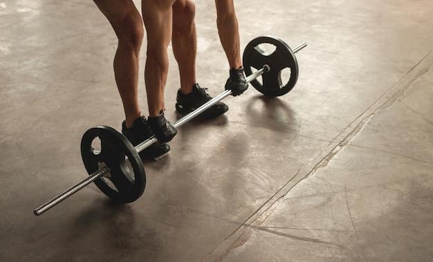 Hoge hoek van anonieme mannelijke atleet barbell opheffen van vloer tijdens gewichtheffen training in de sportschool