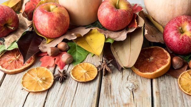 Hoge hoek van appel met gedroogde citrus en herfstbladeren