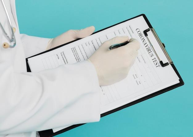 Hoge hoek van arts die coronavirus test invult