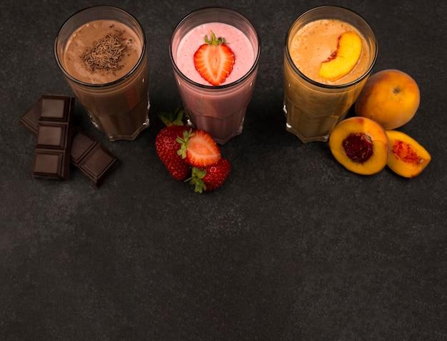 Hoge hoek van assortiment milkshakes met fruit en chocolade