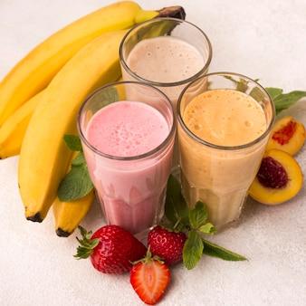 Hoge hoek van assortiment milkshakes met fruit