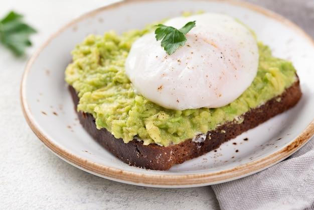 Hoge hoek van avocadotoost met gepocheerd ei bovenop en kruiden